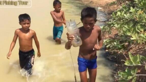 三个小孩子用可乐瓶做起来抓鱼